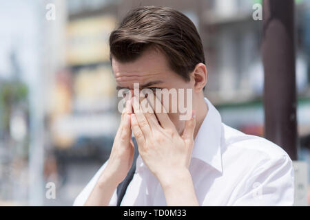 A young man has Itchy, watery, swollen eyes due to pollen allergy - Stock Photo