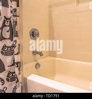 Square Bathtub and shower inside a bathroom with glossy white wall - Stock Photo