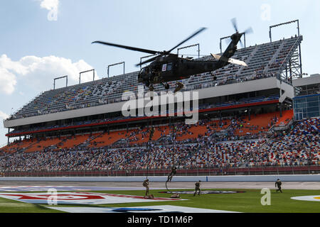U.S. Army paratroopers assigned to the 82nd Airborne Division rappel from a UH-60 Black Hawk helicopter during a ceremony at Charlotte Motor Speedway before the Coca-Cola 600 race in Charlotte, North Carolina, May 26, 2019. The rappelling exercise demonstrated the division's readiness and capability to rapidly respond to contingencies anytime and anywhere. (U.S. Army photo by Spc. Justin W. Stafford) - Stock Photo