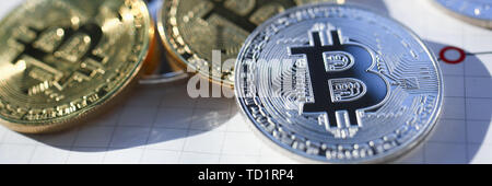 Silver and golden bitcoin on paper graph - Stock Photo