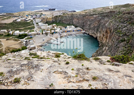 Inland sea (diving spot) with little houses and blue ocean in the background seen from above in gozo, Malta. - Stock Photo
