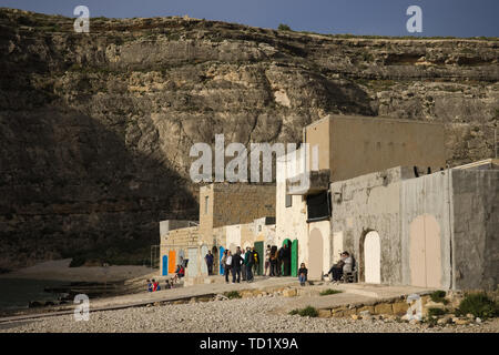 Gozo island, Malta - May 2019: Group of people waiting on the pier of inland sea (diving spot) to look through opening in cliffs. - Stock Photo