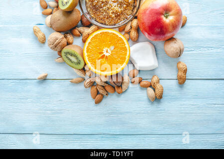 Healthy vegan raw foods on blue wooden background. Fruits and nuts with honey on the table. Natural organic sweet dessert. Place for text - Stock Photo