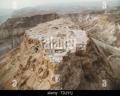 Aerial view of Masada fortress area, ancient fortification in the Southern District of Israel situated on top of isolated rock plateau, akin to a mesa - Stock Photo