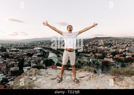 young man on the background of panoramic view of Tbilisi city. - Stock Photo