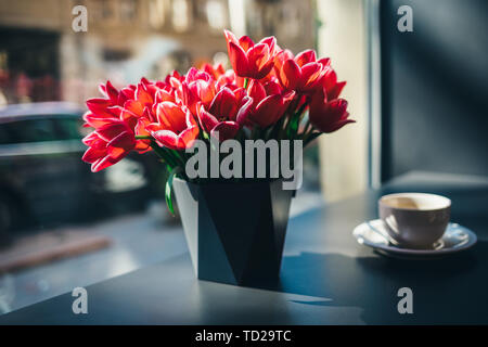 Bouquet of beautiful red tulip flowers in vase on table by the window next to cup of coffee, sun shines through glass. - Stock Photo