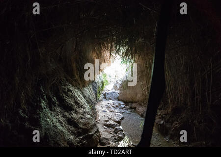 Inside the gloomy cave with damp stone walls and dry grass ceiling supported with stick, the floor has stones and water. Empty human cover in a cave - Stock Photo