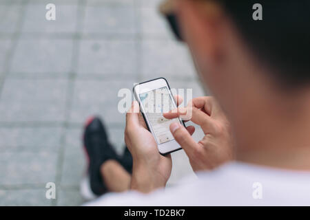 Man looking on navigation map. Travelers using gps map for sightseeing in town - Stock Photo
