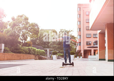 A man in jeans and sneakers on a hoverboard ride in the city. Happy boy riding around at sunset. Modern electronics for relaxation and entertainment
