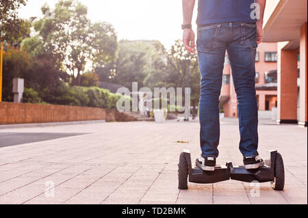 A man in jeans and sneakers on a hoverboard ride in the city. Happy boy riding around at sunset. Modern electronics for relaxation and entertainment - Stock Photo