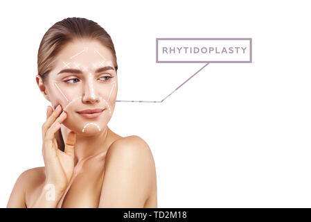 Rhytidoplasty for Anti-Aging. Portrait of attractive young woman with perfect skin and graphic lines and arrows over her face isolated on white background. Plastic surgery concept. Lifting skin concept - Stock Photo