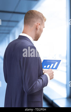 Man in suit inside an office building looking at sales forecast graphics on a tablet computer - Stock Photo