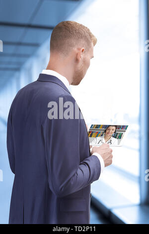 Man with tablet computer in an office building making a video call with doctor, telehealth, telemedicine concept - Stock Photo