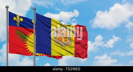 Guadeloupe and Andorra flag waving in the wind against white cloudy blue sky together. Diplomacy concept, international relations. - Stock Photo