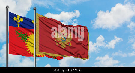 Guadeloupe and Montenegro flag waving in the wind against white cloudy blue sky together. Diplomacy concept, international relations. - Stock Photo