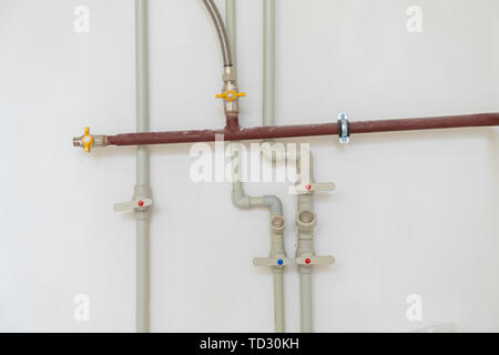 Heating system's cooper pipes with ball valves on a grey wall - Stock Photo