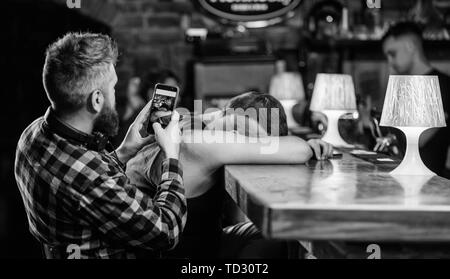 Hipster making fun of drunk friend. Man drunk fall asleep and guy with smartphone. Hipster taking photo drunk friend. Drunk friends in bar. Fall asleep at bar counter. Take photo to remember party. - Stock Photo
