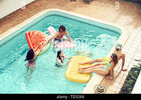 Happy friends having fun in swimming pool during summer vacation - Young people relaxing and floating on air lilos in the pool resort - Stock Photo