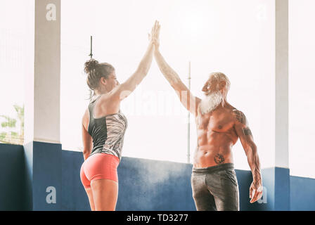 Fitness couple stacking hands in gym wellness club - Happy athletes motivating each other Stock Photo