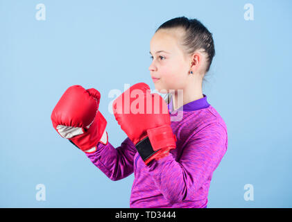 Girl cute boxer on blue background. Contrary to stereotype. Boxer child in boxing gloves. Confident teen. Enjoyment from sport. Female boxer. Sport upbringing. Boxing provide strict discipline. - Stock Photo