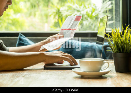 Businessman work on laptop checking invoice with coffee on wooden table. - Stock Photo