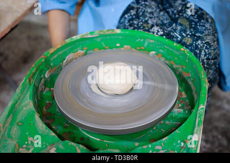 A novice student in the first lesson in pottery tries to make a product from clay on a potter's wheel. reportage. - Stock Photo