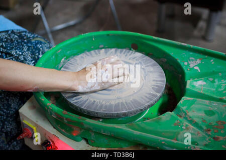 A novice student in the first lesson in pottery tries to make a product from clay on a potter's wheel. reportage - Stock Photo