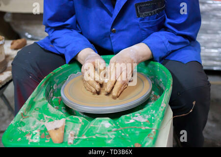 A novice student in the first lesson in pottery tries to make a product from clay on a potter's wheel. reportage. Incorrect hand setting. - Stock Photo