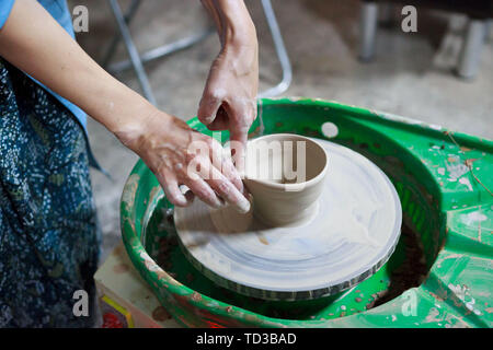 Young woman novice student in the first lesson in pottery tries to make a product from white clay on a potter's wheel. reportage. small sauce pan. mak - Stock Photo