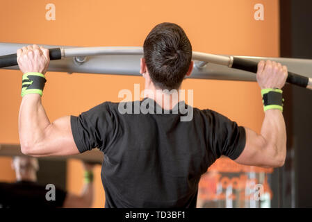 Athlete muscular fitness male model pulling up on horizontal bar in a gym . - Stock Photo