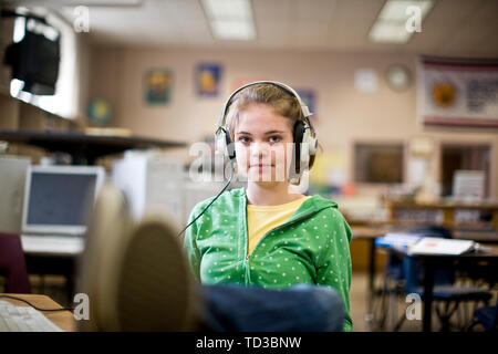 Portrait of a teenage girl in a classroom wearing headphones. - Stock Photo