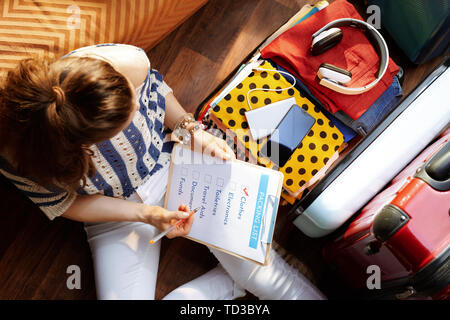 Upper view of elegant woman in white pants and striped blouse with packing list near open travel suitcase at modern home in sunny summer day. - Stock Photo