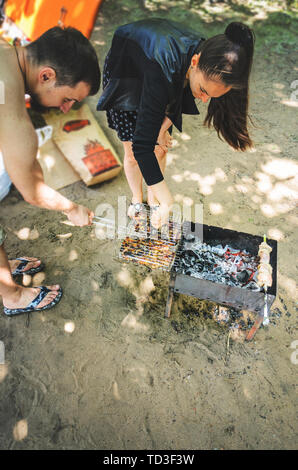 A company of young people cooks meat on the coals view from above.. Beach party barbecue with chicken meat on grid of grill - Stock Photo