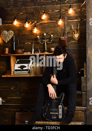 Connection through music. Man bearded musician enjoy evening with bass guitar, wooden background. Man with beard holds black electric guitar. Guy sits - Stock Photo