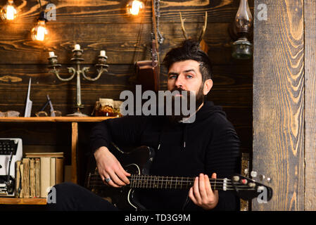 Guitar as hobby. Man bearded musician enjoy evening with bass guitar, wooden background. Man with beard holds black electric guitar. Guy in cozy warm - Stock Photo