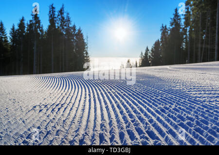 Fresh groomed ski slope close-up against rising sun in the mountains