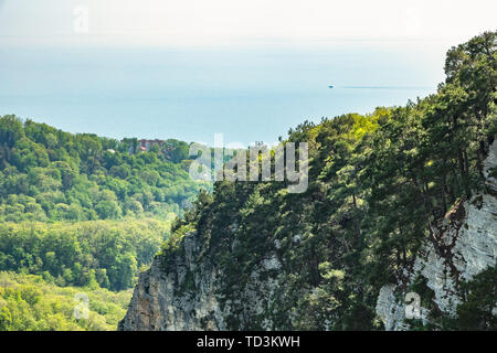 Mountain with a steep rocky slope and valley with thick green forest below. Residential buildings and the sea are visible in the distance - Stock Photo