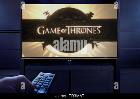 A man points a TV remote at the television which displays the Game of Thrones main title screen (Editorial use only). - Stock Photo