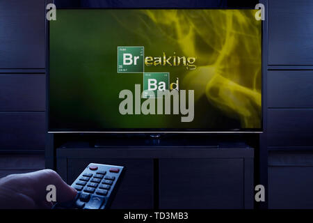A man points a TV remote at the television which displays the Breaking Bad main title screen (Editorial use only). - Stock Photo