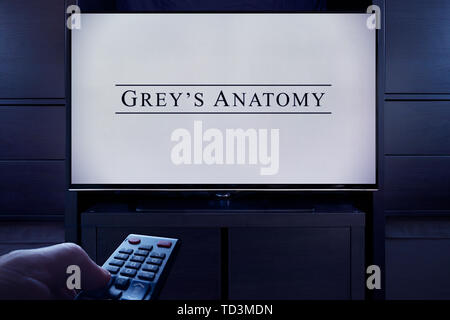 A man points a TV remote at the television which displays the Grey's Anatomy main title screen (Editorial use only). - Stock Photo