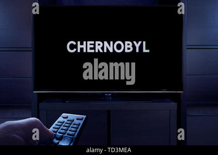 A man points a TV remote at the television which displays the Chernobyl main title screen (Editorial use only). - Stock Photo