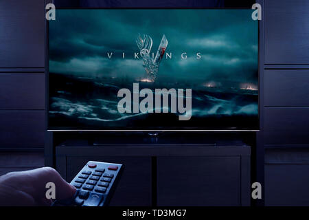 A man points a TV remote at the television which displays the Vikings main title screen (Editorial use only). - Stock Photo