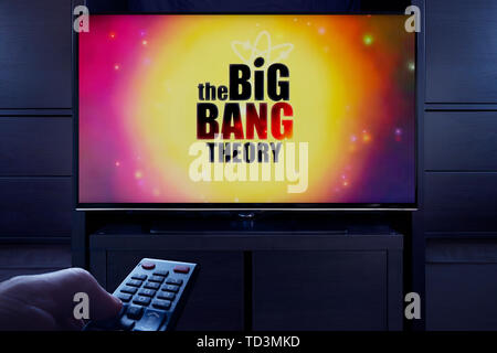 A man points a TV remote at the television which displays the Big Bang Theory main title screen (Editorial use only). - Stock Photo