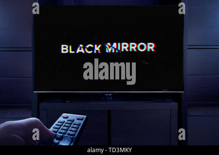 A man points a TV remote at the television which displays the Black Mirror main title screen (Editorial use only). - Stock Photo