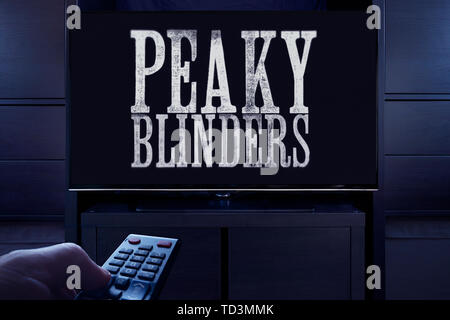 A man points a TV remote at the television which displays the Peaky Blinders main title screen (Editorial use only). - Stock Photo