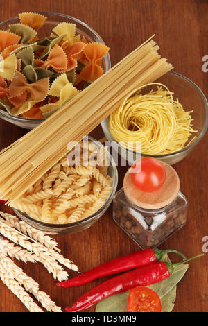 Different types of pasta, spices, tomatoes on a wooden table - Stock Photo