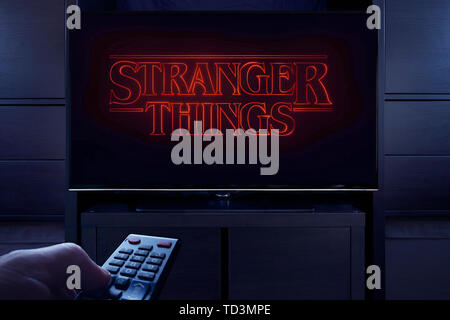 A man points a TV remote at the television which displays the Stranger Things main title screen (Editorial use only). - Stock Photo