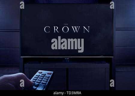 A man points a TV remote at the television which displays the Crown main title screen (Editorial use only). - Stock Photo