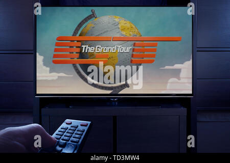 A man points a TV remote at the television which displays The Grand Tour main title screen (Editorial use only). - Stock Photo