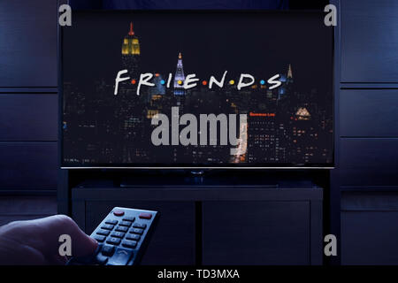 A man points a TV remote at the television which displays the Friends main title screen (Editorial use only). - Stock Photo